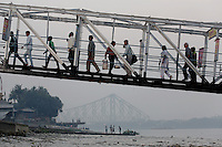 Commuters walk across a small bridge next to the Ganges River in Kolkata, India. November, 2013