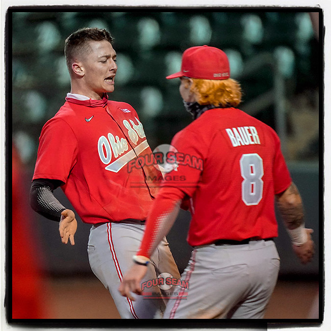 Zach Dezenzo (4) of the Ohio State Buckeyes, left, is greeted after scoring the go-ahead run in a 6-3 13-inning win over the Illinois Fighting Illini on Friday, March 5, 2021, at Fluor Field at the West End in Greenville, South Carolina. (Tom Priddy/Four Seam Images)