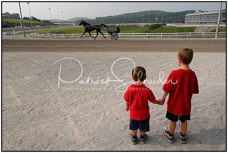Two young boys hold hands as they watch a race horse exercising at a harness race track. Model released, can be used for multiple purposes.