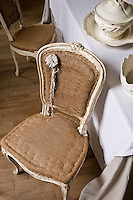 A set of Louis XV dining chairs is revealed in its hessian undercoat