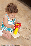 13 month old baby girl at home playing with plastic colored ring and spindle toy