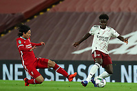 1st October 2020; Anfield, Liverpool, Merseyside, England; English Football League Cup, Carabao Cup, Liverpool versus Arsenal; Bukayo Saka of Arsenal is tackled by Takumi Minamino of Liverpool