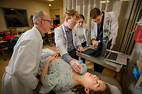 Diagnostic Radiologist Dr. Bradley Cruz teaches Alaska WWAMI Program medical students Zane Davis, Bonnie Snyder, and Evan Gross to use  a portable ultrasound on classmate Hope Spargo as their class learns the basics of ultrasound in UAA's Health Sciences Building.