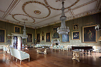 The Great Drawing Room in which two impressive tiered crystal chandeliers hang from a gilded plasterwork ceiling. The walls are covered with a silk damask wall fabric and hung with 18th and 19th century portaits