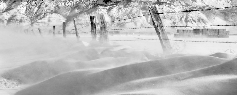 Blowing snow and fence line and Hart Mountain. Warner Valley, Oregon