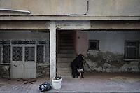 une vieille femme voilée, assise devant chez elle, dans une rue d'Adiyaman.