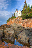 Bass Harbor Head Lighthouse is reflected in a tidal pool as it overlooks the entrance to Bass Harbor and Blue Hill Bay in Tremont, Maine.