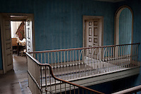 The walls of the abandoned top floor landing are a delightful faded blue stripe