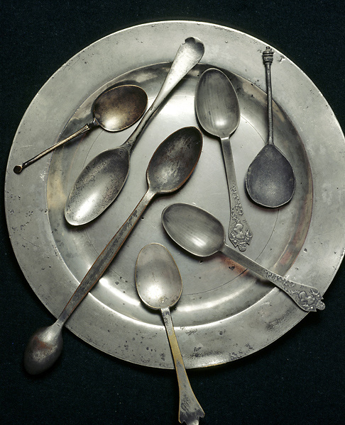 A plate and spoons from the extensive pewter collection of 400 items displayed in the Corridor. Some of the spoons have decorated handles.