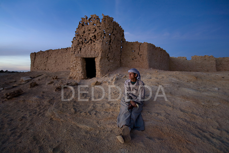 A local, young Siwan man relaxes in an abandoned mudbrick village on the outskirts of Siwa Town in the Siwa Oasis, Egypt, at dusk.
