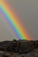 A rainbow shines over new lava rock in Kalapana just after sunrise, Big Island.