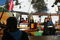 Switzerland. Valais. Crans Montana. Winter ski resort. Lunch time at open air restaurant. A giant bottle of Veuve Cliquot brut champagne stands on the bar. A waitress is carrying a plate with a sandwich. Sunny day. © 2005 Didier Ruef