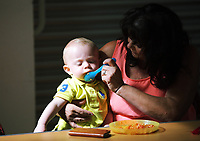 Pictured: Heather Maynard (R) feeds one year old Lincoln at St Teilo Church in Clase, Swansea, UK. Friday 25 August 2017<br /> Re: Free food for children story, Swansea, Wales, UK.