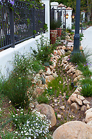 Rock lined streetside sidewalk storm water and water capture rain garden for percolation in summer-dry garden; design Urban Water Group, Los Angeles