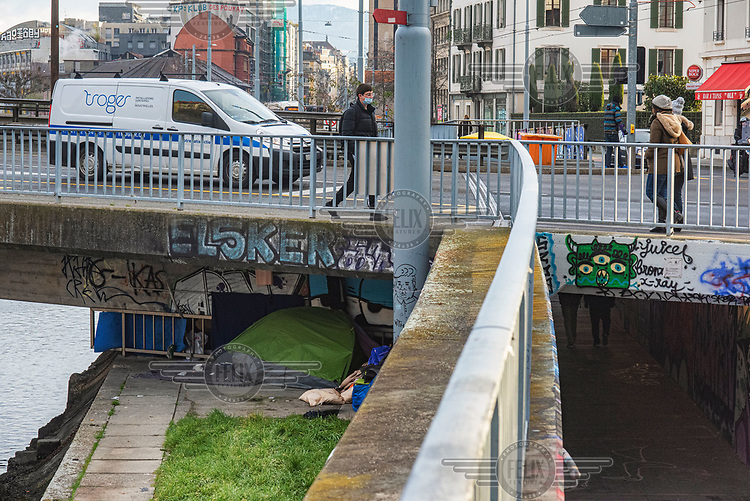 Tents of the homeless hidden from sight under one of the bridges across the Rhone River as it runs through Geneva.