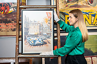 BNPS.co.uk (01202 558833)<br /> Pic: MaxWillcock/BNPS<br /> <br /> Pictured: Sale Coordinator Lulu Randall with a motoring poster printed for the 1994 Tour de Auto featuring an image of Michael Wright's watercolour of the Tour de France Automobile 1971 race, in the Dreweatts Donnington Priory saleroom.<br /> <br /> A glamorous collection of early French motorsport posters has emerged for sale with a British auction house for £25,000.<br /> <br /> The earliest examples date from 1900 showing well-heeled Parisians chauffeured in vintage cars on the capital's streets.<br /> <br /> The vehicles are flanked by marching bands with passengers in their finest clothes to reinforce the element of prestige.<br /> <br /> There is a striking 1902 French poster of a British Mulberry car in the Scottish Highlands, while another celebrates the 1934 Grand Parade Vichy.