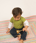 Baby boy 12 months old sitting holding brass bell and ringing it