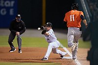 Charlotte Knights first baseman Joe DeCarlo (10) stretches for a throw as Ryan Ripken (11) of the Norfolk Tides hustles down the line while umpire Alex Tosi looks on at Truist Field on May 14, 2021 in Charlotte, North Carolina. (Brian Westerholt/Four Seam Images)