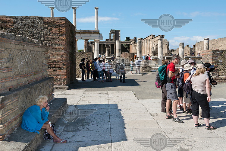 Tourists at the archeological site of Pompeii, the Roman city buried under 4 to 6 metres of ash and pumice by the eruption of Mount Vesuvius in 79 AD. By 2008, it was attracting almost 2.6 million visitors per year, making it one of the most popular tourist sites in Italy.