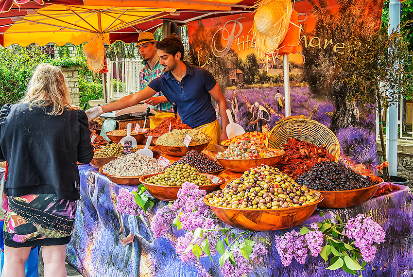 Olives and other goodies are for sale at a stand at the busy Sunday market in Saint-Cyprien, a small village near Sarlat-la-Canéda in Périgord, département Dordogne, France