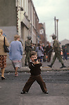 Ireland The Troubles. Belfast young boy with toy gun. British soldier patrols street behind. Downtown urban shopping street Belfast. 1980s<br />