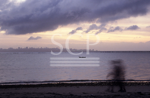 Itaparica Island, Bahia, Brazil. Two men walking along the beach at dawn, fishing canoe and Salvador in the background.
