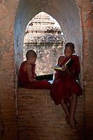 Myanmar, Burma. Bagan.  Two Novice Monks Reading in a Temple Window.