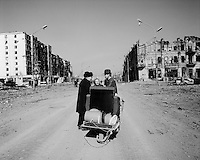 Grozny, Chechnya, March 1995..A resident carrying belongings on a wheelbarrow in the ruined city centre..