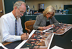 "Historian Ron James and former first lady Dema Guinn sign prints of Steven Saylor's ""Nine Cheers for the Silver State"" artwork, at the Capitol, in Carson City, Nev., on Wednesday, Sept. 24, 2014. Dignitaries featured in the painting will sign the 150 limited edition prints which will be sold as a fundraiser for the Comstock Foundation for History and Culture.<br /> Photo by Cathleen Allison"