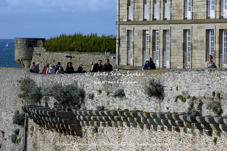 Tourists walking along the ramparts of the old fort at Saint-Malo, Brittany, France.