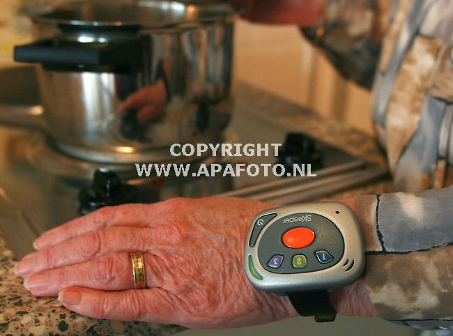 Tolkamer 181006 Een bejaarde bewoonster van verzorgingstehuis Lobede in Tolkamer gebruikt een Diafoon om haar pols. Dit apparaat waarschuwt wanneer bv het gas aan blijft staan.<br /> Foto frans Ypma APA-foto