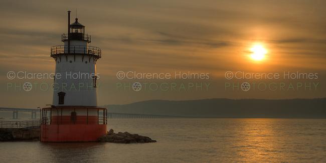 Tarrytown Lighthouse on the Hudson River under a hazy sky near sunset.