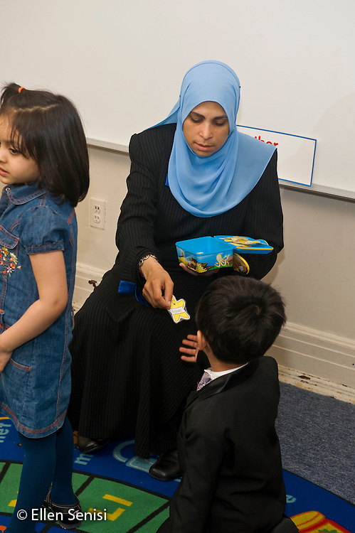 MR / Jersey City, NJ.Al-Ghazaly Elementary School (private Islamic school with a curriculum that follows state curriculum content standards and also teaches Islamic studies) / Pre-K classroom.Teacher (Egyptian-American, wearing hajib) gives a student (boy; 6; Pakistani-American, dressed in suit) his name card. He will place it at the learning center he wants to use..ID: AI_gPag  MR: Lye1 Hal4 Asl1.© Ellen B. Senisi