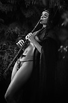 Sensual black and white portrait of a beautiful sexy Native American tribal woman playing a bamboo flute in the nature with her half nude body shining in dim light Image © MaximImages, License at https://www.maximimages.com