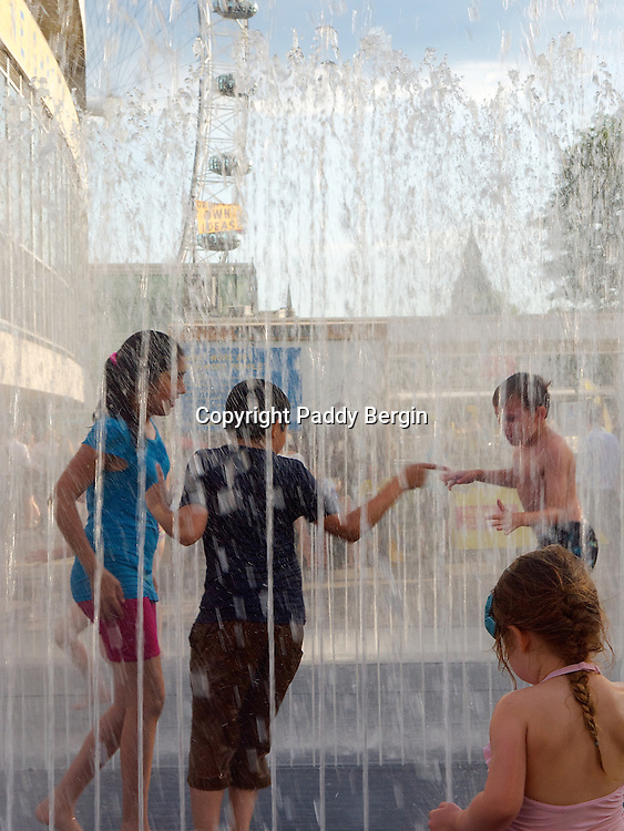 """Children playing in a splash fountain outside the Royal Festival Hall, South Bank, London. London Eye in the background.<br /> <br /> A splash fountain or bathing fountain is intended for people to come in and cool off on hot summer days. These fountains are also referred to as interactive fountains. These fountains are designed to allow easy access, and feature nonslip surfaces, and have no standing water, to eliminate possible drowning hazards, so that no lifeguards or supervision is required. These splash pads are often located in public pools, public parks, or public playgrounds (known as """"spraygrounds"""").<br /> <br /> Stock Photo by Paddy Bergin"""
