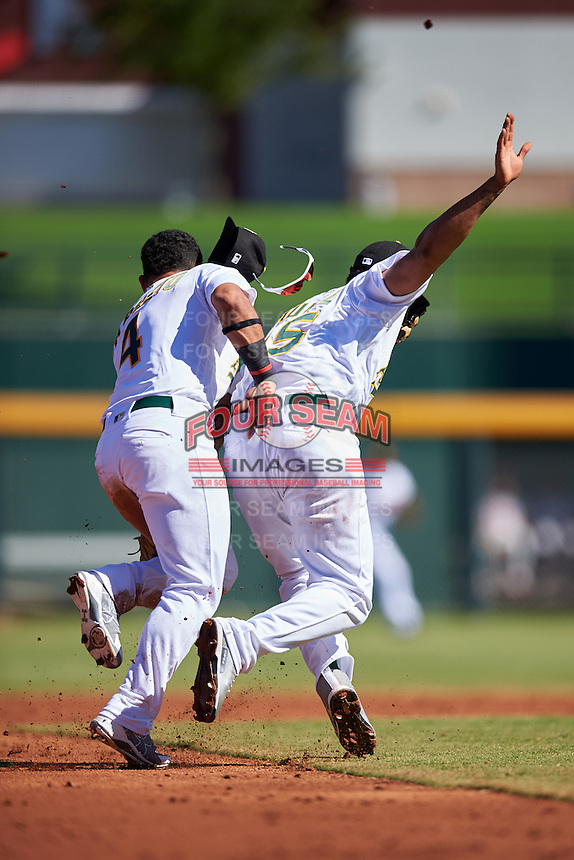 Mesa Solar Sox Franklin Barreto (4) and Yairo Munoz (15), both of the Oakland Athletics organization, collide while going for a ground ball during a game against the Scottsdale Scorpions on October 18, 2016 at Sloan Park in Mesa, Arizona.  Mesa defeated Scottsdale 6-3.  (Mike Janes/Four Seam Images)