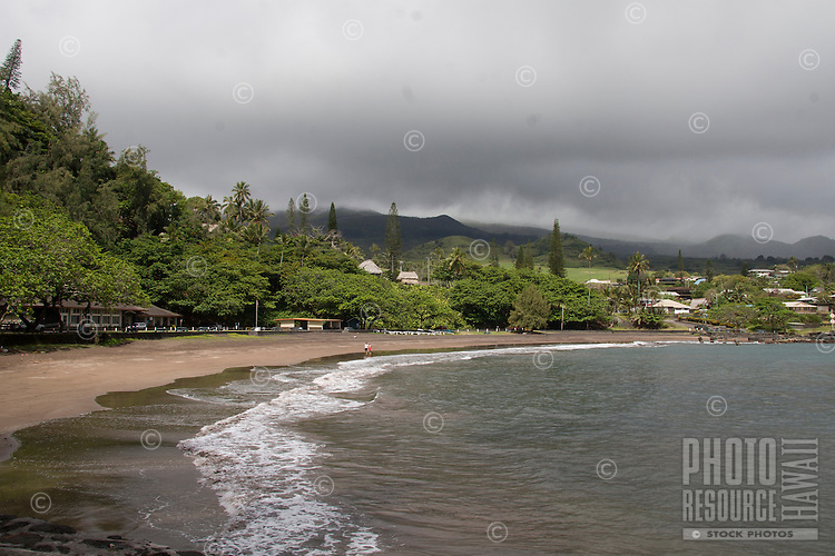 A couple walks along the shore of Hana Bay Beach Park on cloudy day, Hana, Maui.