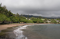 A couple walks along the shore of Hana Bay Beach Park on cloudy day, Hana, Maui.