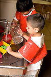 Education preschoool children ages 3-5 water play two boys in smocks playing with water at sink vertical