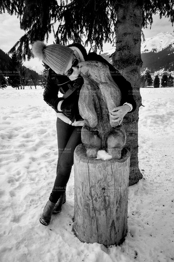 Switzerland. Canton Graubünden. Davos. Winter scene with snow covering the landscape. Carla Burani Ruef kisses a beaver's wooden sculpture. The beaver (genus Castor) is a large, primarily nocturnal, semiaquatic rodent. Castor includes two extant species, the North American beaver (Castor canadensis) (native to North America) and Eurasian beaver (Castor fiber) (Eurasia). 25.01.2020 © 2020 Didier Ruef