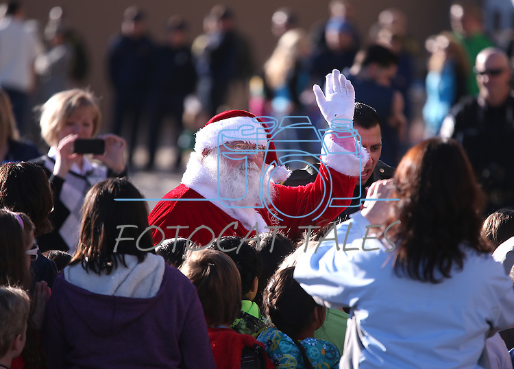 Santa greets kids at the 10th annual Holiday with a Hero event at Walmart in Carson City, Nev., on Wednesday, Dec. 17, 2014. The event pairs 200 of Carson City's K-5th grade homeless students with a local heroes for Christmas shopping. <br /> Photo by Cathleen Allison