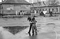 Refugee children from Bosnia play in the yard of a refugee camp in Varazdin in the rain.