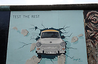 "Germany, Berlin, The wall, East side gallery, wall paintíngs and murals about the cold war and walls, painting with east german car Trabant ""Trabbi"" breaking through the wall by Birgit Kinder"