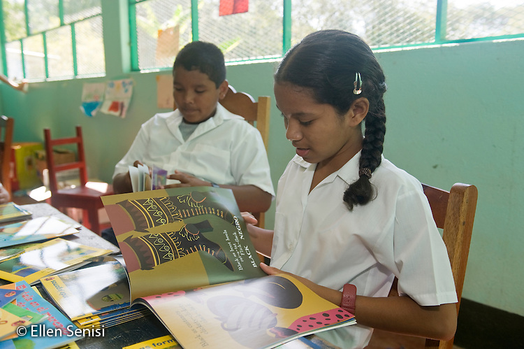 Guanacaste, Costa Rica.Santa Marta School.Two students look at new books in the classroom. Students (boy, 9 and girl, 8, Costa Rican) wear their school uniforms..© Ellen B. Senisi
