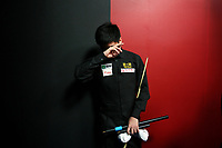 CHINA. Beijing. Chinese snooker player Ding Junhui backstage just before going to play at the China Snooker Open. Ding faces massive pressure as China's number 1 snooker player. He is as famous as Jackie Chan and Yao Ming and is always expected to perform. He famously broke down in tears during one match in 2007. Snooker is a cue sport played on a large table measuring 3.6 metres x 1.8 metres. Originating in India in the late 19th Century where it was invented by British Army officers, the game has been a mainstay in British sport over the past few decades. Recently however, popularity of the sport has declined as the sport struggles to compete with other popular sports. The sport is however flourishing in countries such as China, where it is now the second most popular sport, behind Basketball. In a country where the  players are treated like movie-stars, China may be the great hope for the sports recovery. 2009