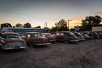 The rear bumpers of cars from 60 and 70 years ago, lined up and glowing under sunset light along a mainstreet, USA.