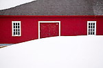A red barn with white windows and a snow drift during the winter in Quebec, Canada.