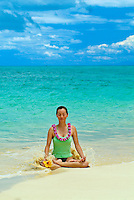 Woman meditating in lotus position wearing flower lei with small wave washing up around her on white sand beach in Hawaii