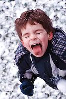 Boy (6-8) catching snowflake on tongue, close-up (digital enhancement)