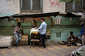 A customer gets a hair cut at a street barber stall in the BBD Bagh area of Kolkata, India, on Friday, May 26, 2017. Photographer: Sanjit Das